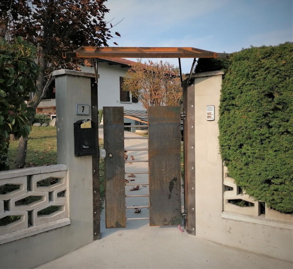 cancello pedonale in Corten e sbarre in acciaio inox con pensilina
